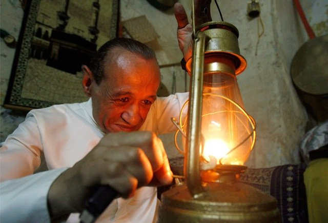 A Musaharati, dawn awakener, lights up a lantern before touring the streets with his drums to wake observant Muslims for their overnight 'sahur', last meal, before the day's fast in Sidon's Old City in south Lebanon just before dawn August 26, 2009.