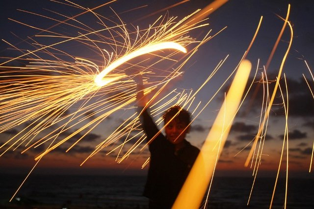 A Palestinian boy plays with a sparkler on the eve of the Muslim holy fasting month of Ramadan in Gaza City on August 21, 2009.
