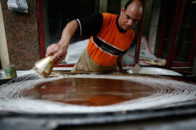 """An Egyptian man makes a traditional dessert known as """"kunava"""", which is popular during the fasting month of Ramadan, at a shop in Cairo August 25, 2009."""