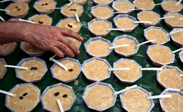 A Muslim man arranges bowls of a traditional dessert called kheer for sale outside a mosque before the evening prayers on the first day of the holy month of Ramadan, in Jammu, Jammu and Kashmir, Indian-administered Kashmir on August 23, 2009.
