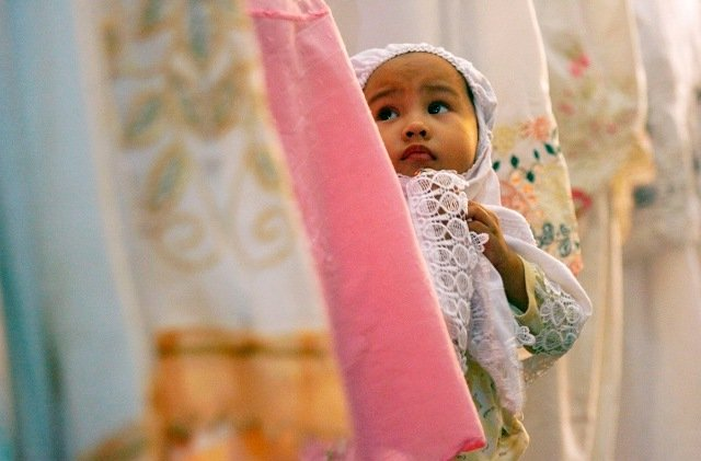A child stands among worshippers attending prayers on the eve of the first day of the Islamic fasting month of Ramadan at Al Maerkaz Al Islami mosque in Makassar, South Sulawesi, Indonesia on August 21, 2009.