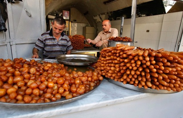 Palestinian vendors prepare trays of sweets for Ramadan, in a shop in the West Bank city of Nablus, Sunday, Aug. 23, 2009.