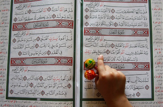 A boy holds candy in his hand as he reads the Quran in a mosque during Ramadan, in Amman, Jordan on August 22, 2009.