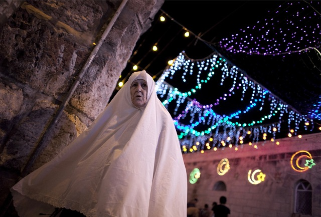 A Palestinian woman walks near the Lion's Gate in Jerusalem's old city where traditional festive lights are displayed ahead of the start of the Muslim holy month of Ramadan on August 20, 2009.