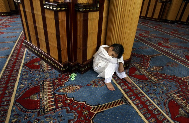 """A Muslim boy takes a nap during evening prayers called """"Tarawih"""" at Mosque of Gamal Abdel Nasser in Tripoli, Libya on August 22, 2009. The mosque was converted from the Catholic Cathedral of the Sacred Heart of Jesus after a 1969 coup by Libyan leader Muammar Gaddafi."""