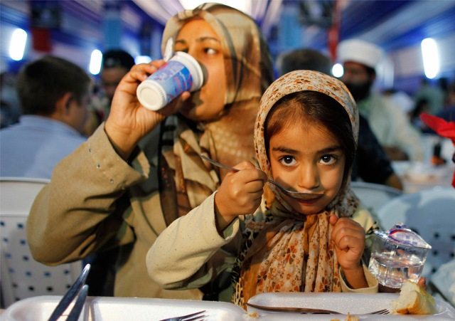A Muslim family eats, breaking their fast in a giant tent on the first day of the holy month of Ramadan in Istanbul, Turkey on August 21, 2009.