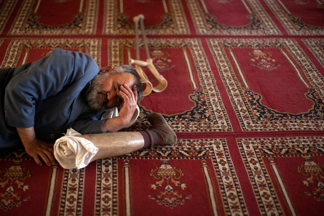 A man takes a nap in between prayers at a mosque in Kabul, Afghanistan on August 22, 2009.