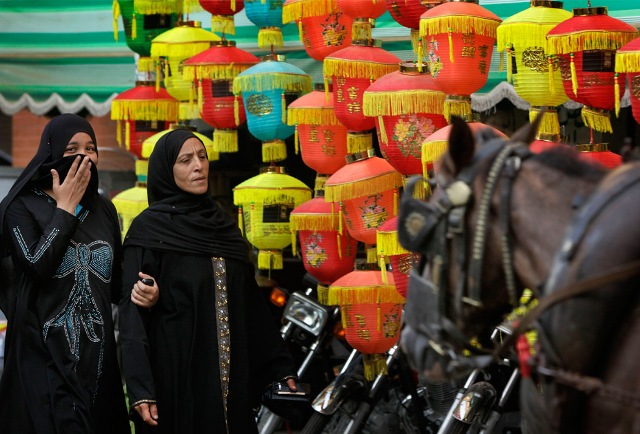 Egyptian women walk past paper lanterns used as decorations during Ramadan, on a street in downtown Cairo, Egypt on Wednesday, Aug. 19, 2009.