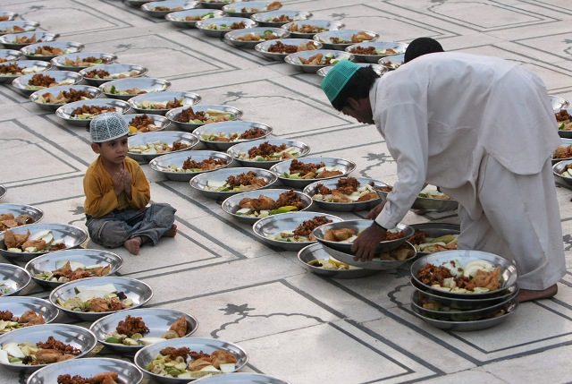 A Pakistani Muslim arranges food stuff for Iftar, a time to break the fast, on the first day of Ramadan, as a child looks on at a mosque in Karachi, Pakistan on Sunday, Aug. 23, 2009.