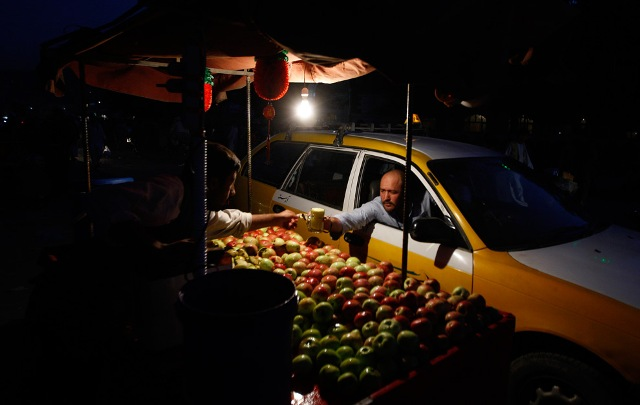 A taxi driver reaches for a glass of apple juice after sunset in Kabul, Afghanistan on Sunday Aug. 23, 2009.